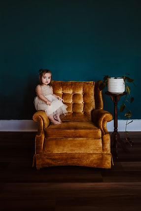 Little girl sitting in a yellow chair toddler session in owensboro ky