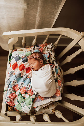 Newborn sleeping in chair with colorful quilt