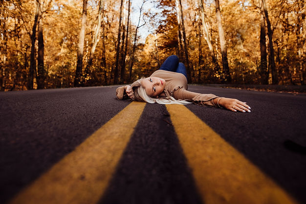 Girl laying in the road looking back senior session in owensboro ky