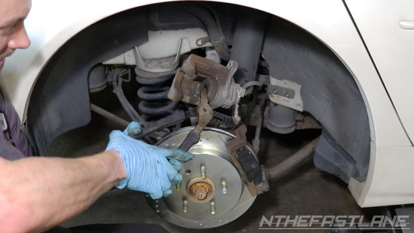Compressing brake caliper piston with grove joint pliers