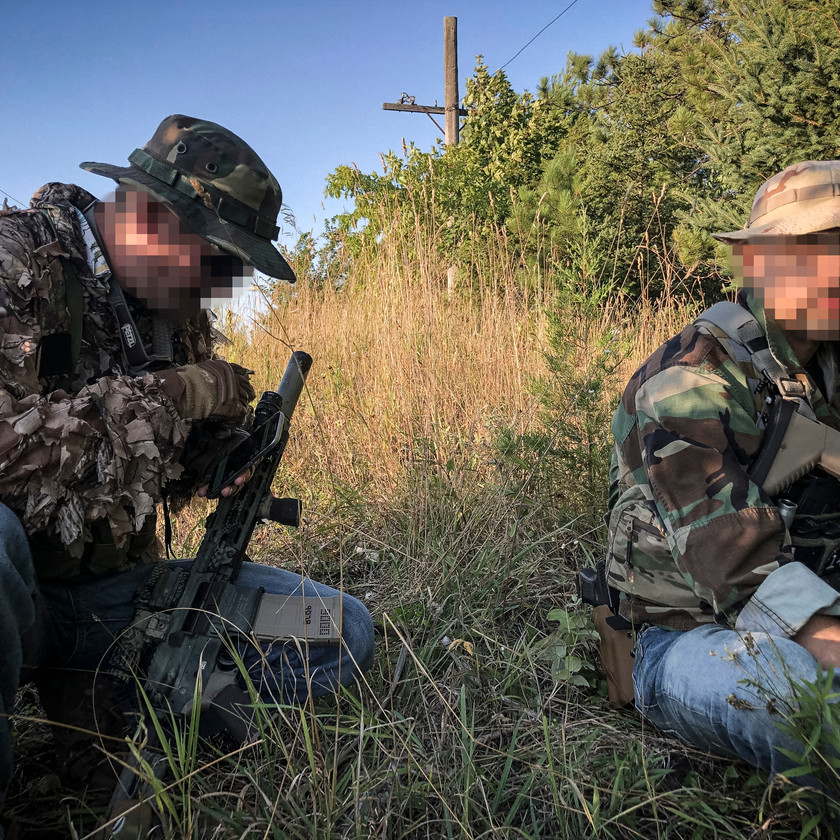 Blackline Simulations Airsoft Milsim - Ruby Echo - Hawaiian shirt liaison team resting in field with airsoft guns and jeans