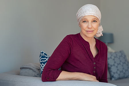Mature woman with cancer in pink headscarf smiling sitting on couch at home. woman sufferi