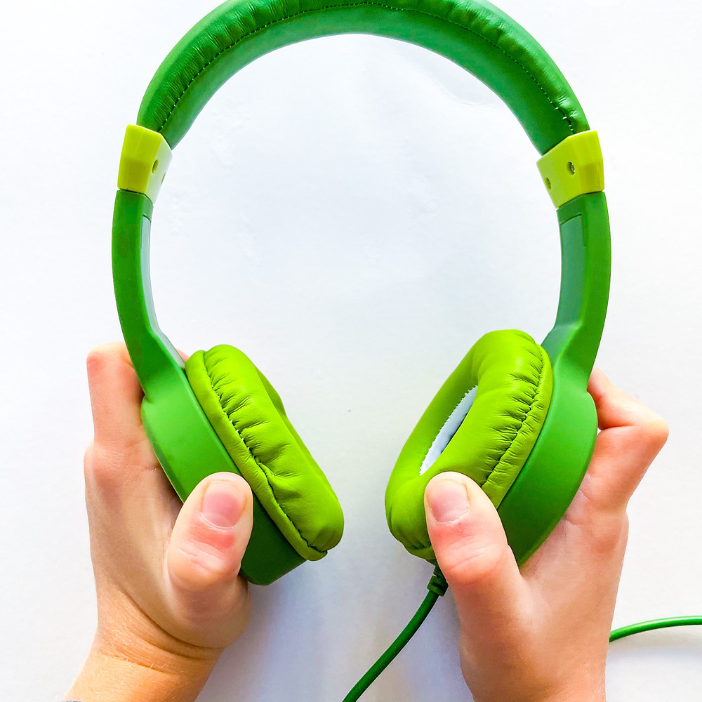 Hands with green kids headphones - daily 5 listening to reading