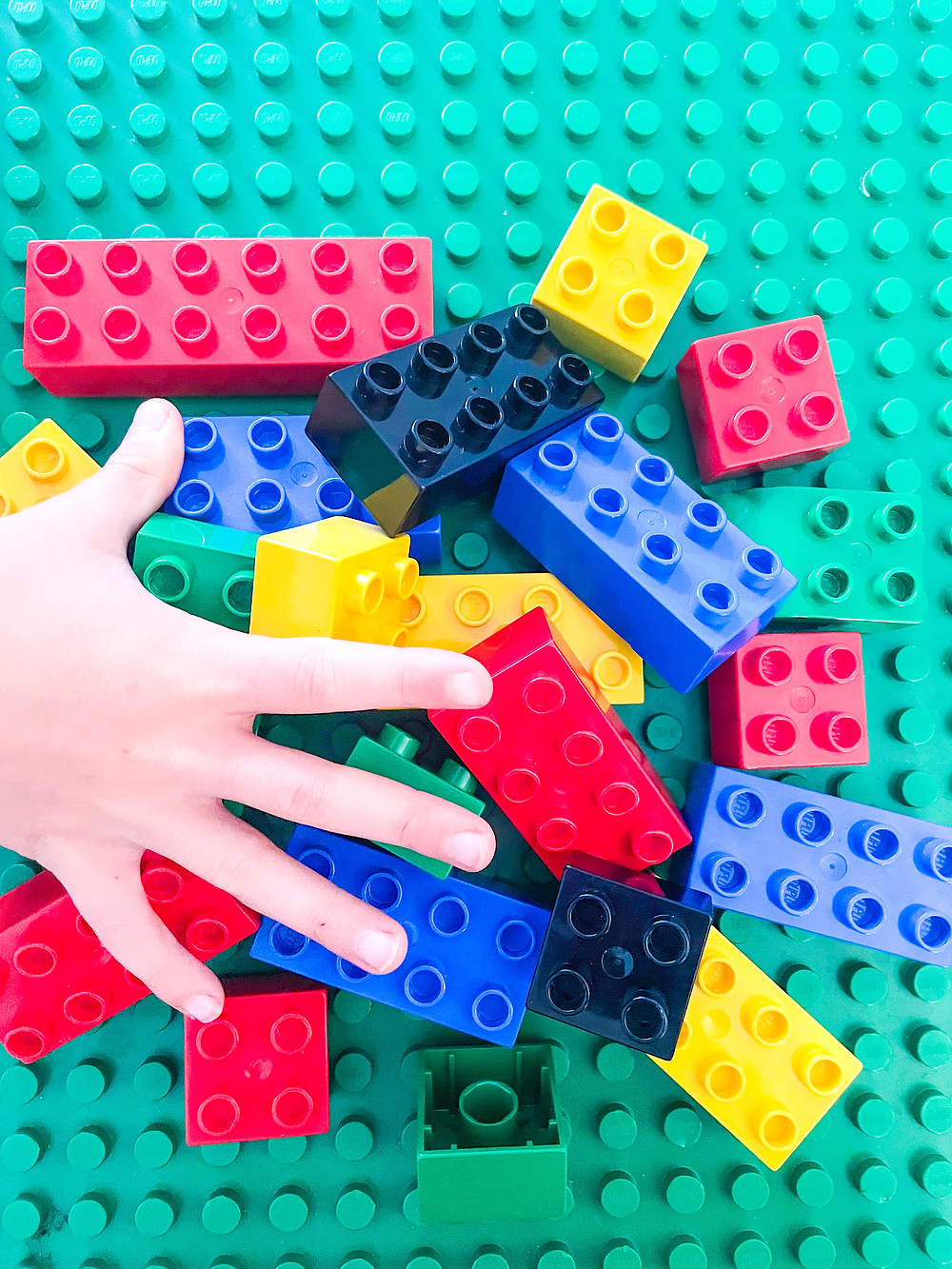 Hand with duplo blocks in Olympic colours