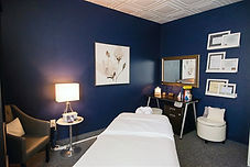 Massage Studio with massage table, chair, lamp, rolling stool, desk, ottoman and license display