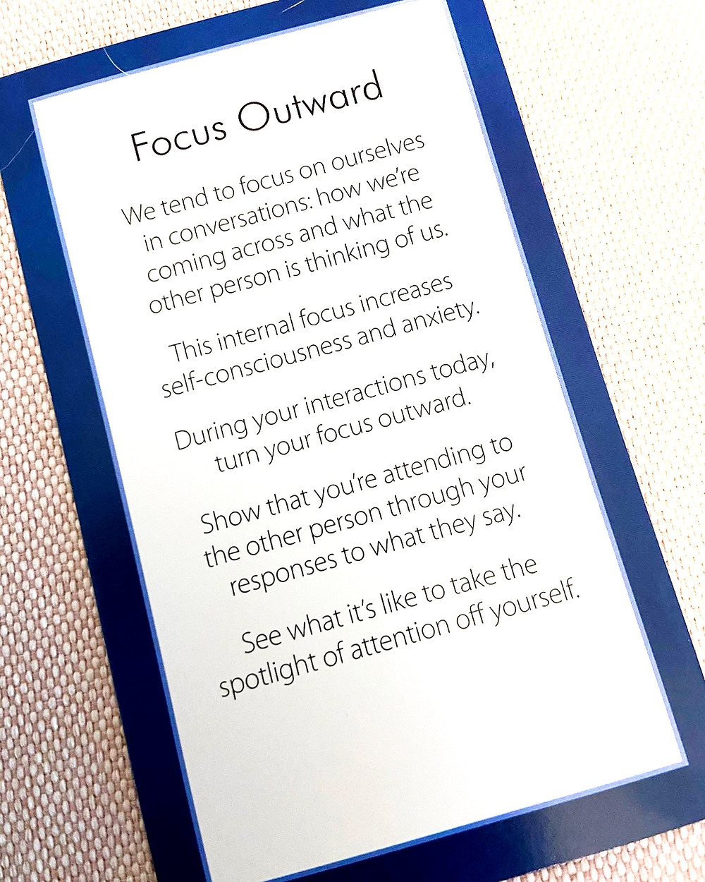 """Card with blue background that reads """"Focus Outward. We tend to focus on ourselves in conversations; how we're coming across and what the other person is thoinking of us.  This internal focus increases self-consciousness and axiety.  During your interactions today, turn your focus outward.  Show that you're attending to the other person through your responses to what they say.  See what it's like to take the attention off yourself."""""""