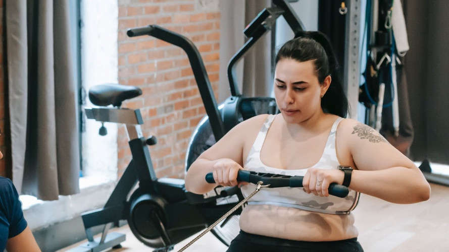 Woman in Cropped Sports Tank and Black Pants Working Out on Rowing Machine with other workout equipment in the background