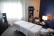 Massage Studio with large window, massage table, hot towel caddy, side table, lamp, rolling stool