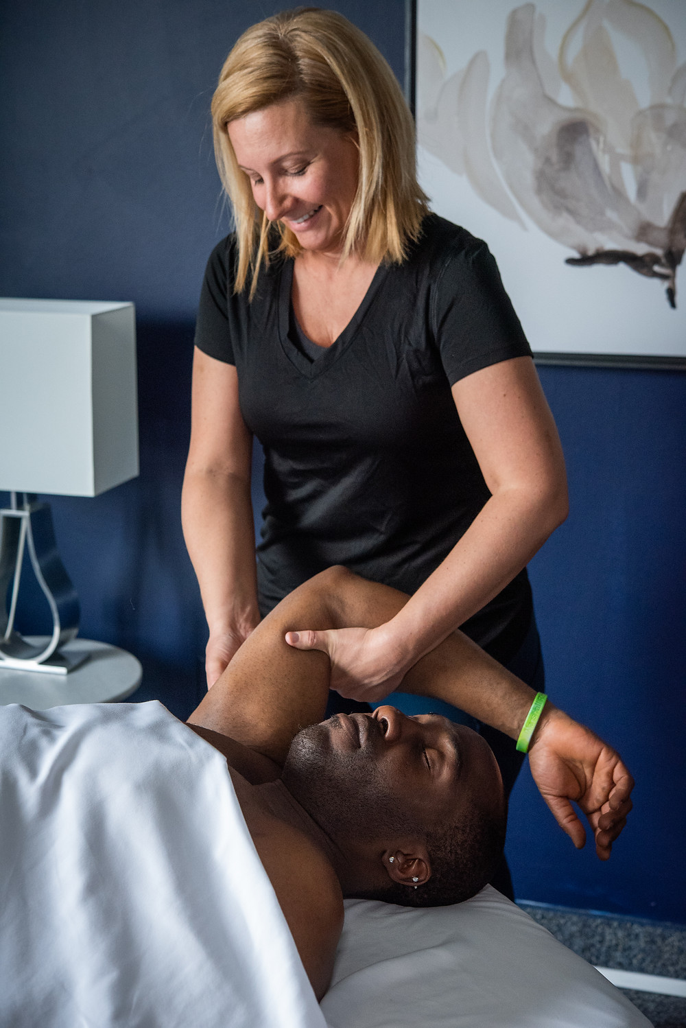 Photo of Abe Koroma in Massage Setting with techniques performed to triceps & biceps performed by Meg Donnelly, LMT
