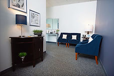 Reception and waiting area featuring 4 dark blue plush chairs, lamp lighting on dark wood tables side tables.