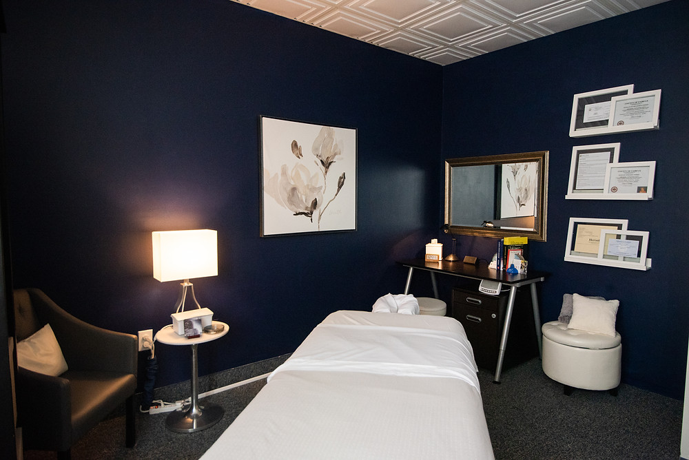 Massage Studio of Meg Donnelly, LMT including Soothing Dark Blue Walls, Contrasting White Pictures, Soft Lighting, Clean White Beveled Squares Ceiling, Faux Leather Seating and Linen Dressed Electric Massage Table