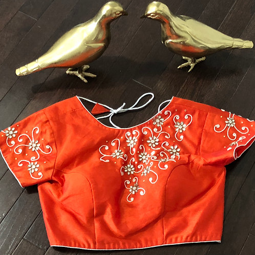 Orange blouse white beads .
