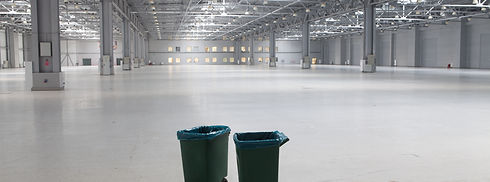 Two dustbins in large modern storehouse.