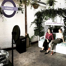 two stylish women in a studio style photo booth with bespoke tropical backdrop