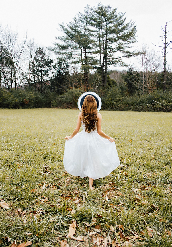 bride in a field with the photo booth