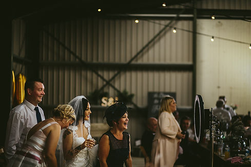 bride with guests using a photo booth at a warehouse wedding in Northumberland, North East.