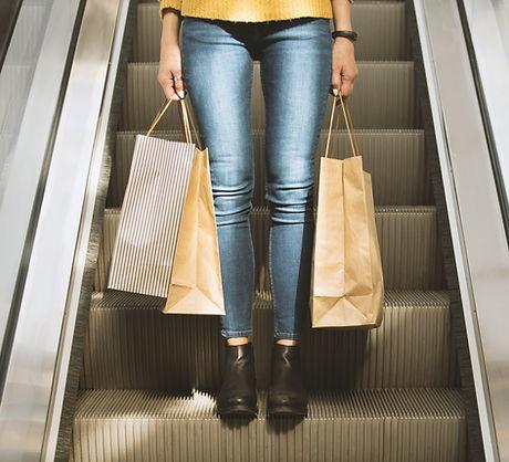 Muchacha que sostiene bolsos de compras