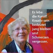 Gunhild Scharpf, Malerin. Steht vor ihrem Bild. Das Bild ist farbenfroh. Orange, rot und Pink
