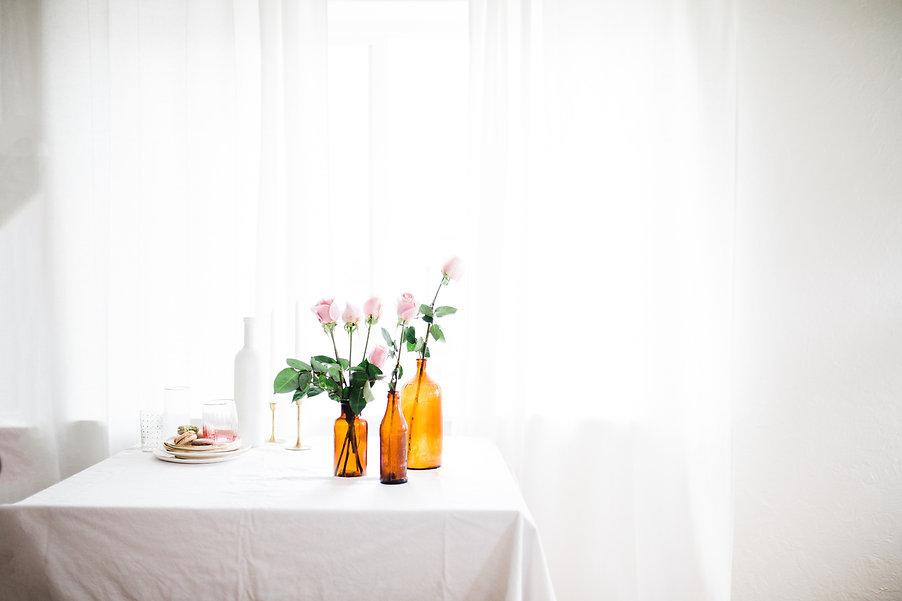 espace avec une entrée de lumière et des voilages. En premier plan une table avec des bouteil...oses