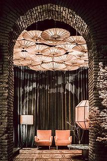espace d'accueil avec un plafond en ombrelles roses éclairées et des fauteuils en velours roses