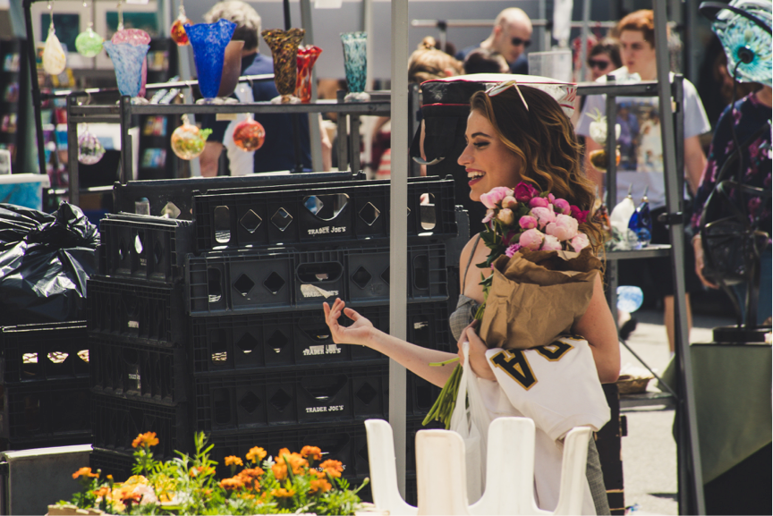 Smiling girl shopping at barcelona flower market preparing for an event