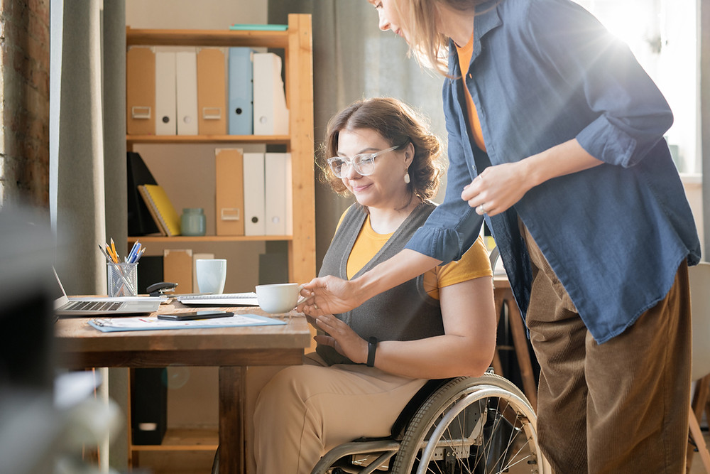 working-woman-being-brought-coffee-by-support-person-or-carer