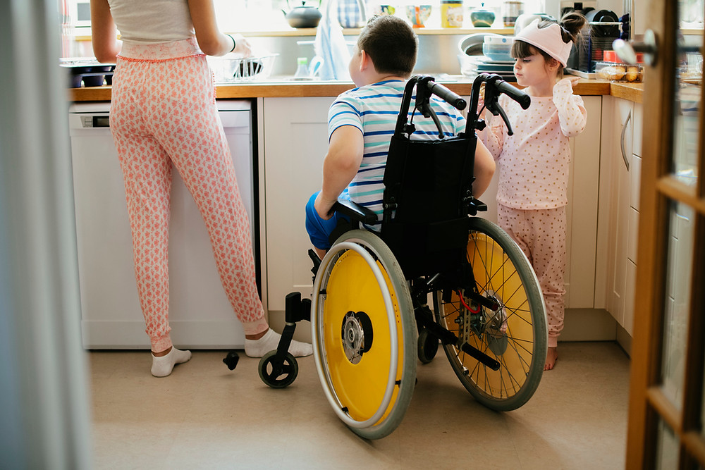 Young-boy-in-a-wheelchair-in-the-kitchen-with-his-family-doing-the-dishes