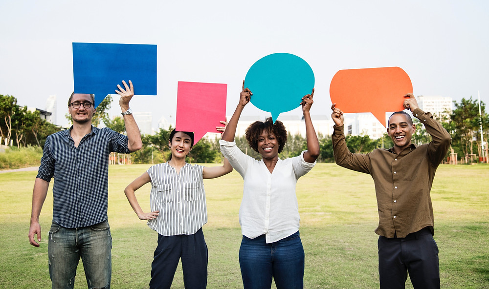 Four adults holding blank coloured speech bubbles and smiling