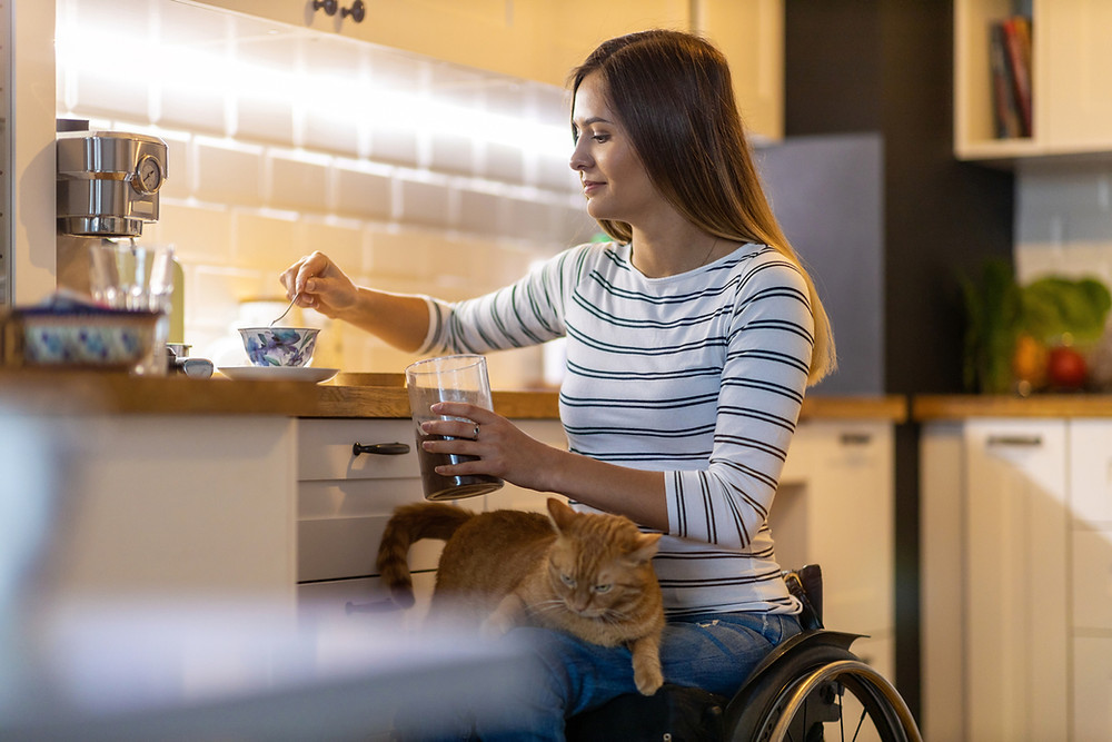 Woman-in-wheelchair-preparing-tea-with-cat-on-her-lap