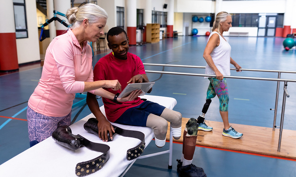 Woman-physiotherapist-assisting-young-man-with-disability
