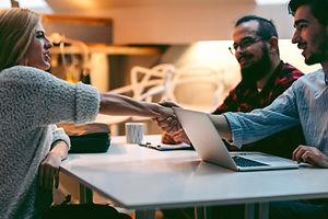 Woman shaking hand across a desk