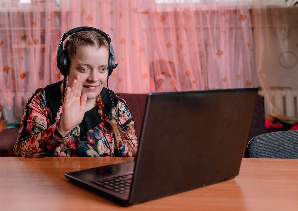 Young woman with disability in meeting on her laptop