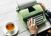 Young milleial writes a letter to Congress on a typewriter while drinking green tea