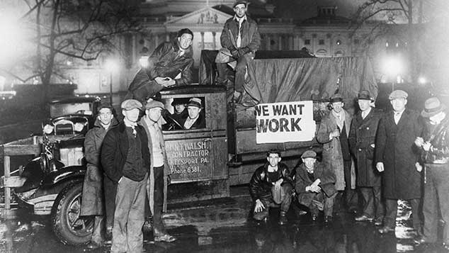 """Unemployed men posing around a truck, with a sign saying """"WE WANT WORK"""""""
