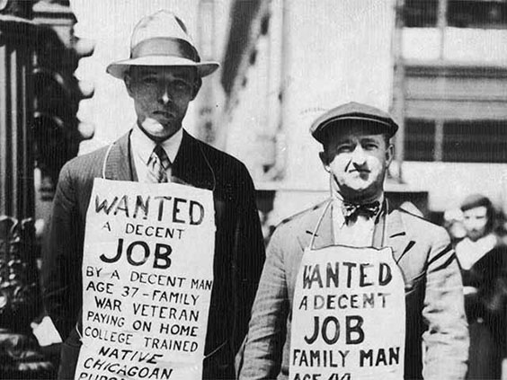 """Two unemployed men wearing signs with the words """"Wanted, A Decent Job"""", and personal information on them."""