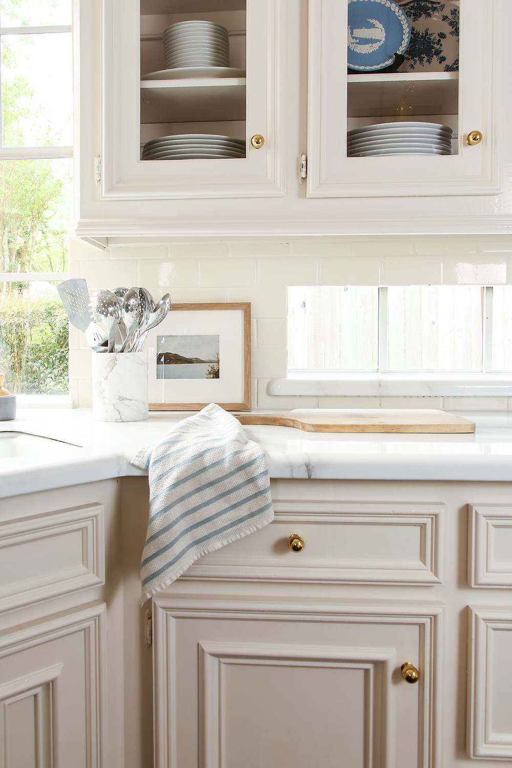 white and blue kitchen with marble countertops