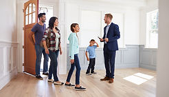 real-estate-agent-showing-house-family.j