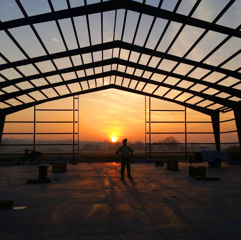 Man standing under metal-framed building