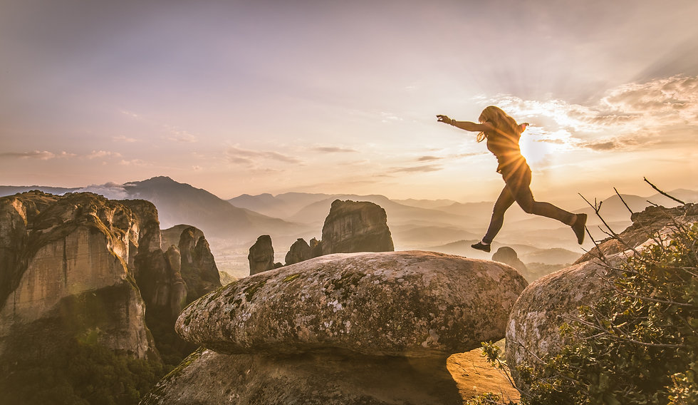 woman-jumping-over-rocks-in-front-of-a-s