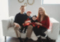 Family dressed in red and black sitting on a white couch