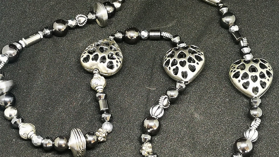 Long necklace with silver coloured hearts.