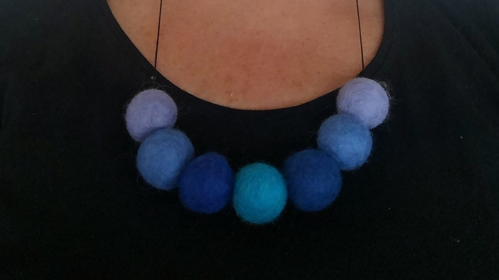 Felt ball necklace in shades of blue.