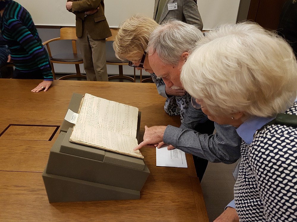 People looking at manuscript book
