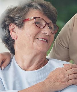 Professional helpful caregiver comforting smiling senior woman at nursing home_edited_edit