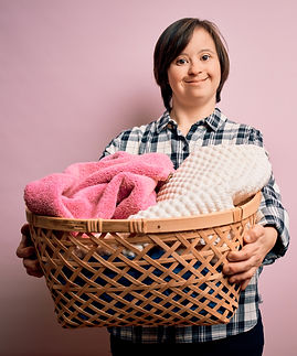 Young down syndrome woman doing housework domestic chores holding laundry wicker basket wi