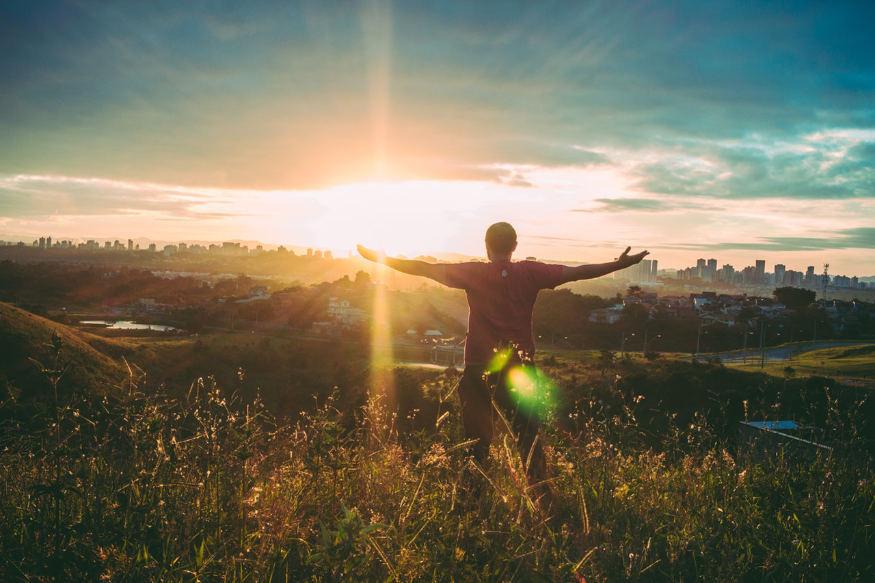 wolność finansowa i mężczyzna stoi przodem do Słońca.