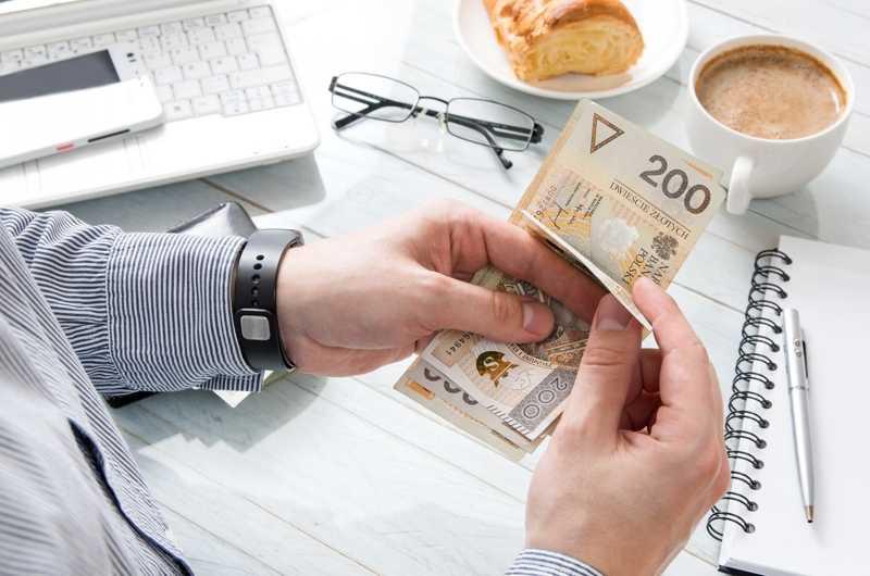 Mężczyzna liczy banknoty dwustuzłotowe - wydatki