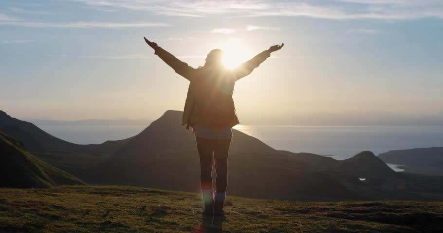 Wolność finansowa i kobieta stoi w górach twarzą do Słońca.