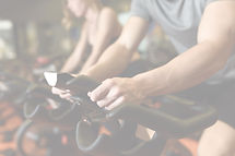 Close-up of hands of a man biking in the gym, exercising legs doing cardio workout cycling bikes. Co