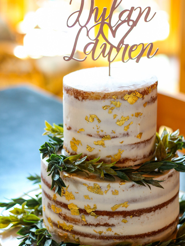 Naked cake with edible gold leaf, greenery and a custom topper. Photo Copyright Wildflour Cake Design